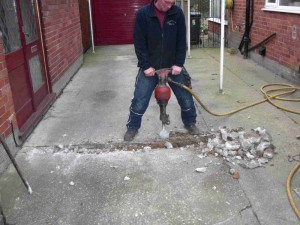 Digging up the driveway using a jack hammer.